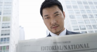 Asian man reading newspaper