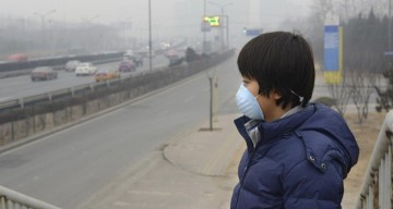 Person wearing air filter mask in smoggy city